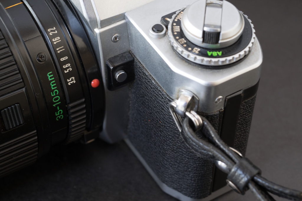 Canon AV-1 - the button on the top plate is the battery check. The button on the side of the reflex chamber is for exposure compensation